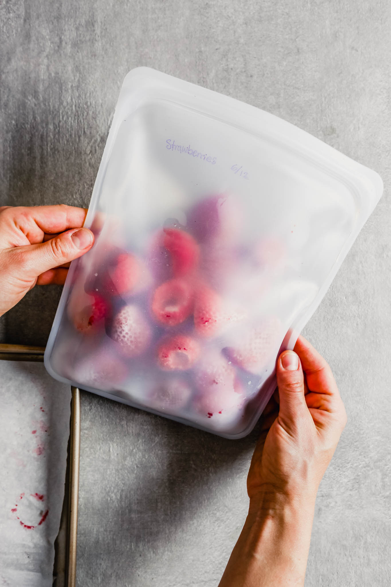 Overhead photograph of a reusable resealable bag filled with frozen whole strawberries