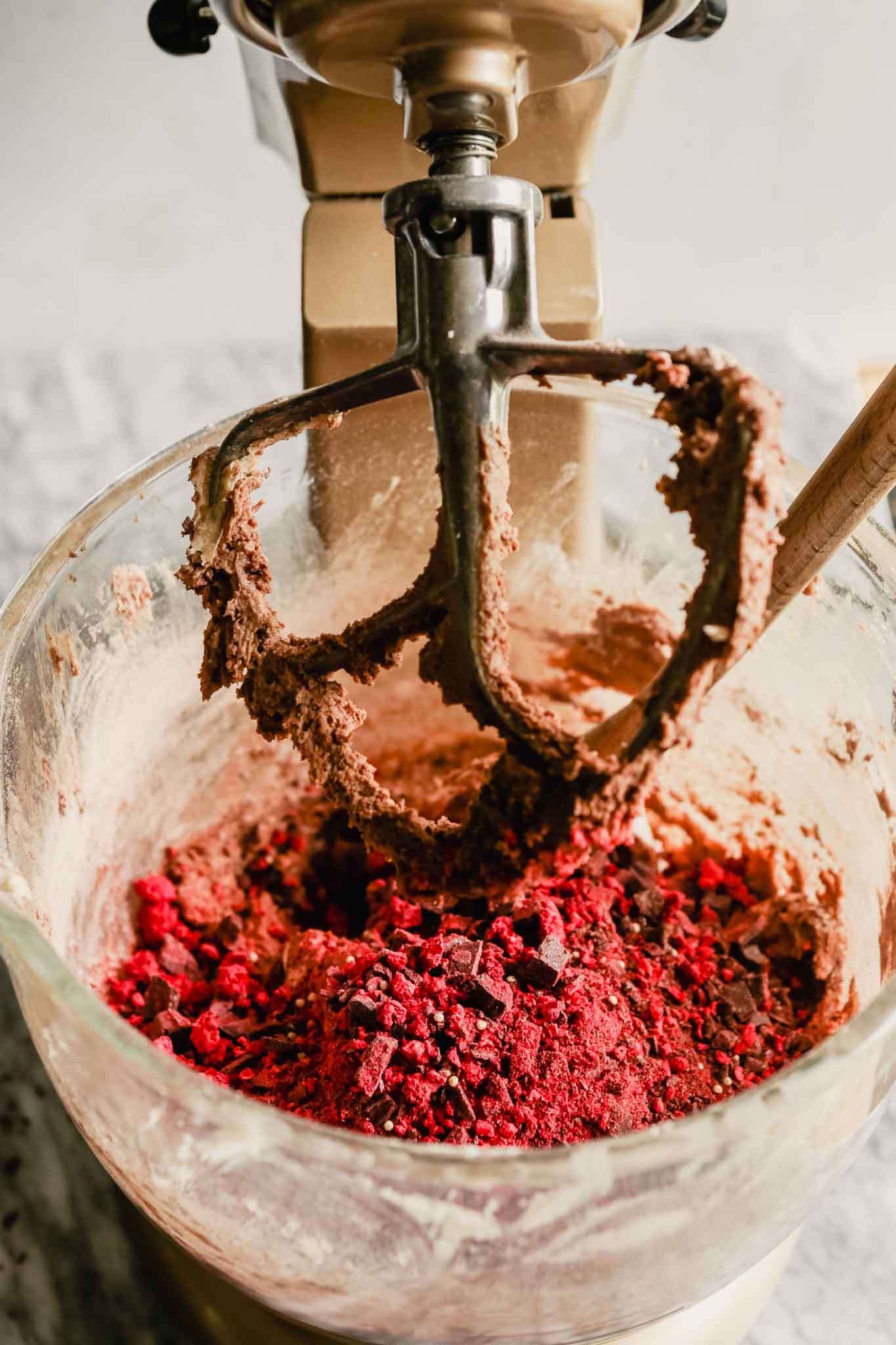 Freeze dried raspberries, millet and mexican chocolate in a mixing bowl with chocolate cookie dough