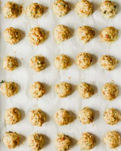 Overhead photograph of baked chicken meatballs on a parchment lined baking sheet