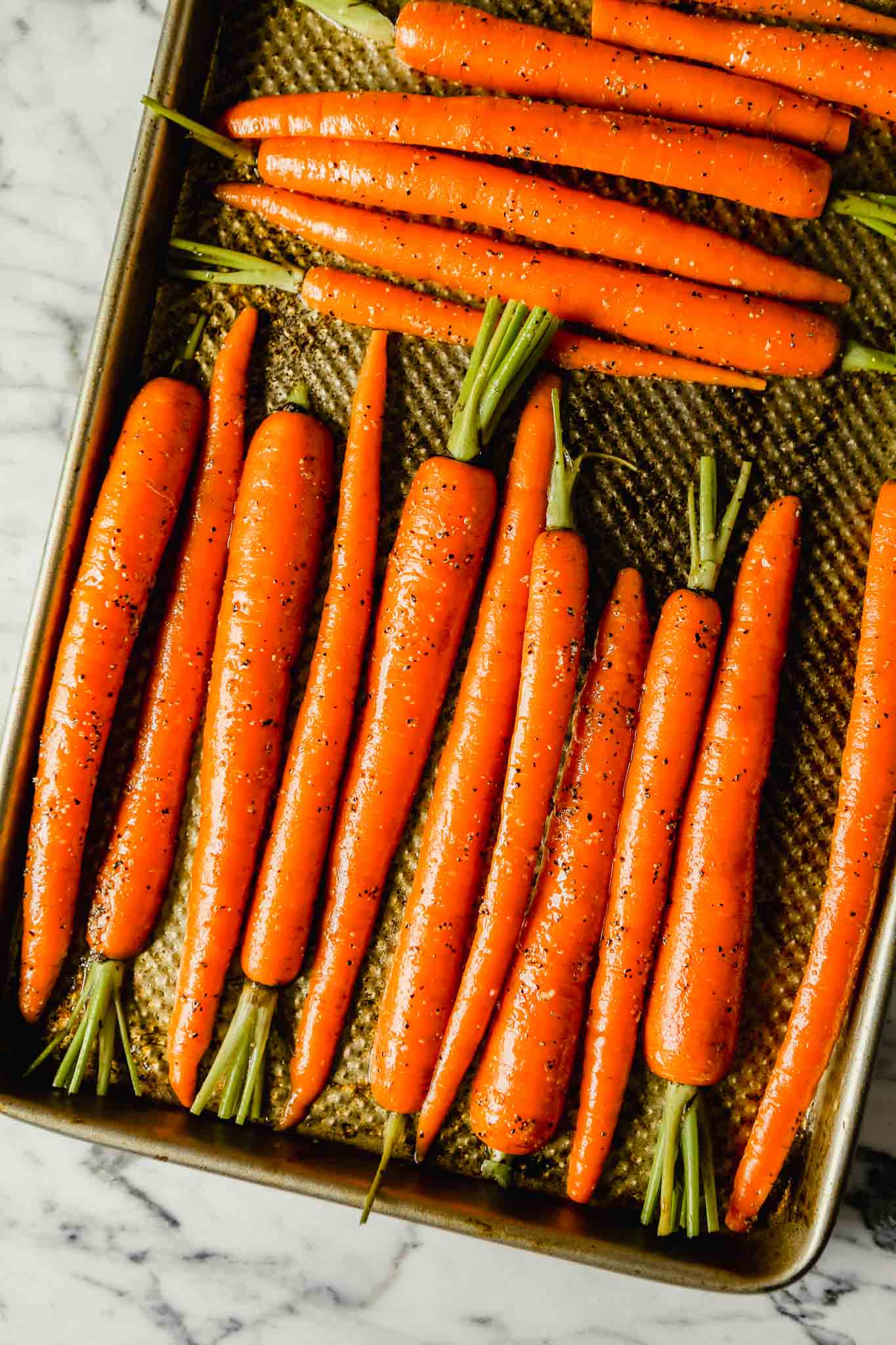 Photograph of halved carrots on a baking sheet