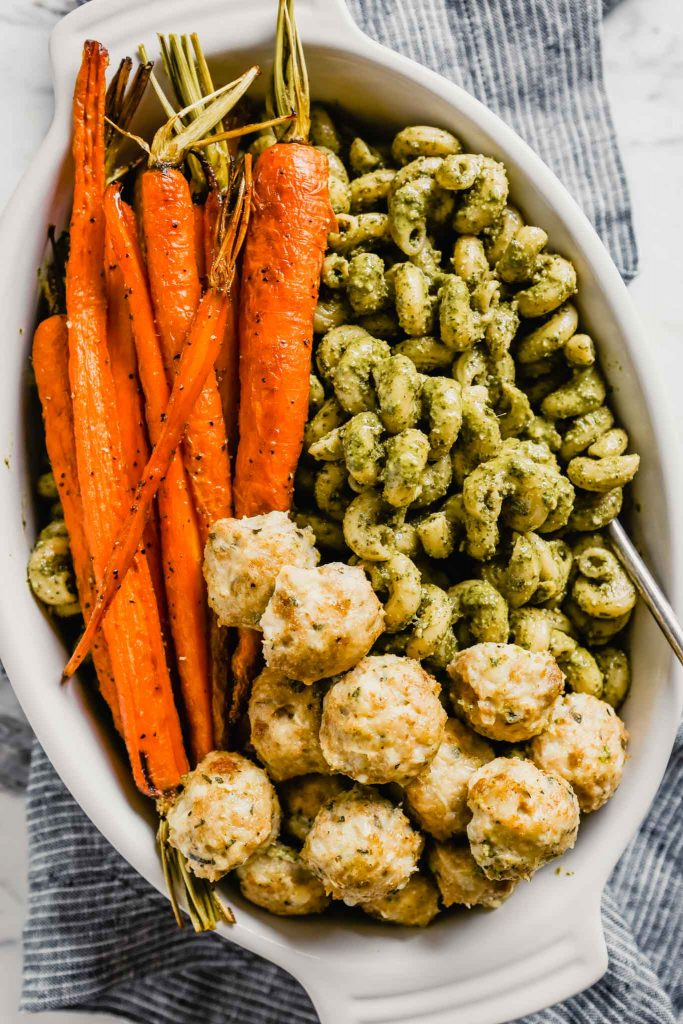 Photograph of a white baking dish filled with pesto pasta, roasted carrots and baked chicken meatballs