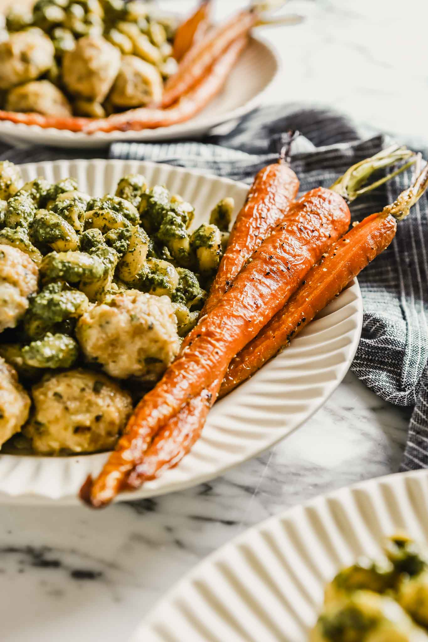 Photograph of chicken meatballs in a white bowl with pesto pasta and roasted carrots