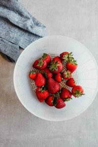 Photograph of fresh strawberries in a plastic basket