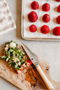 Photograph of hulled fresh strawberries on a parchment paper-lined baking sheet
