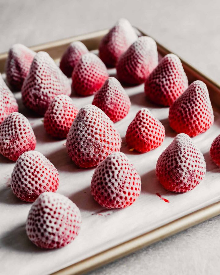 Photograph of frozen whole strawberries arranged on a baking sheet
