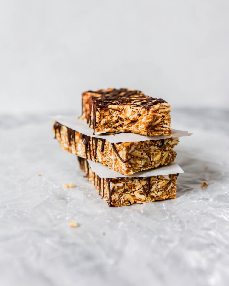 Photograph of homemade chewy granola bars stacked on top of each other on wax paper on a marble table.