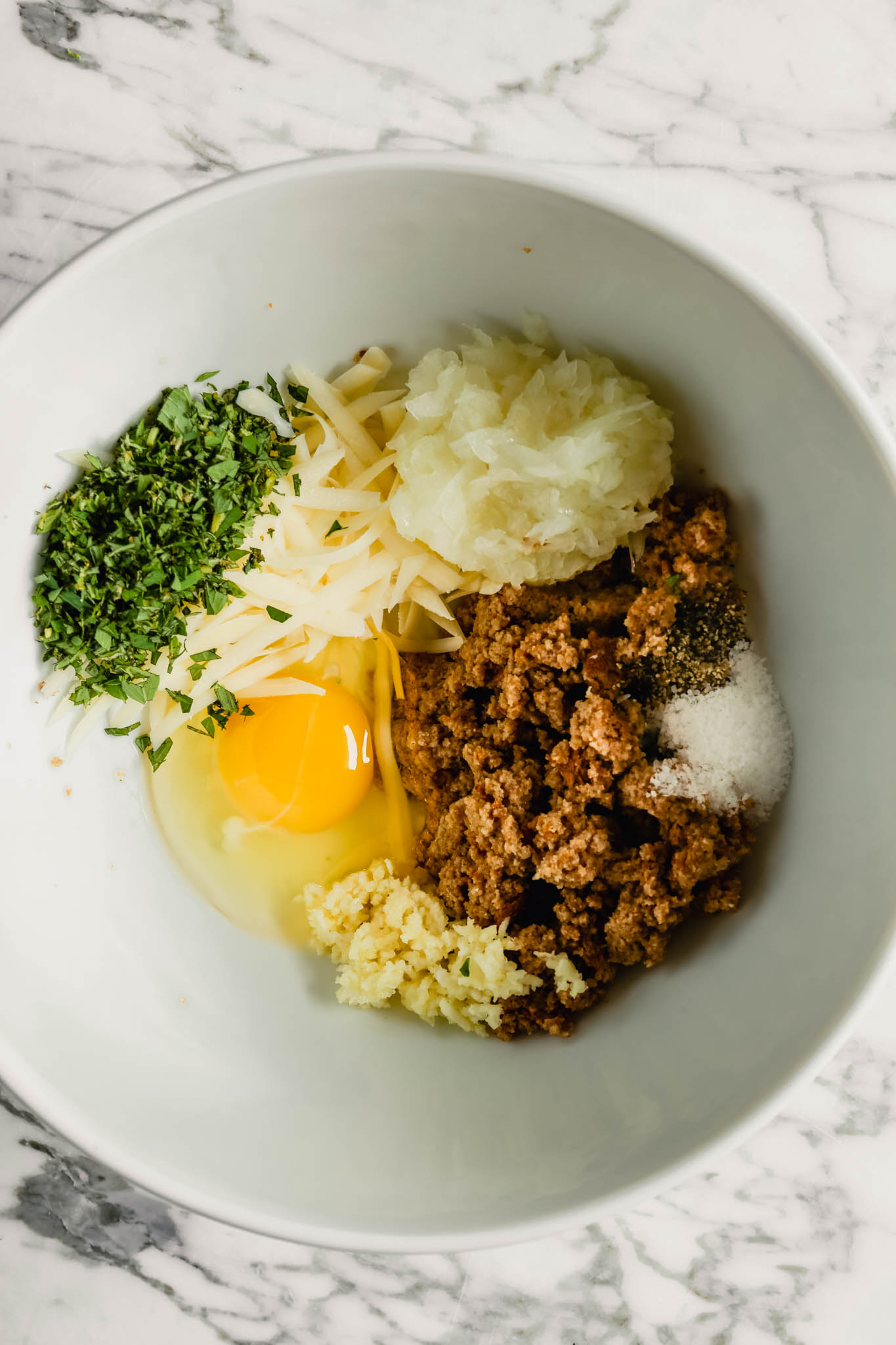Photograph of meatball ingredients in a large white bowl