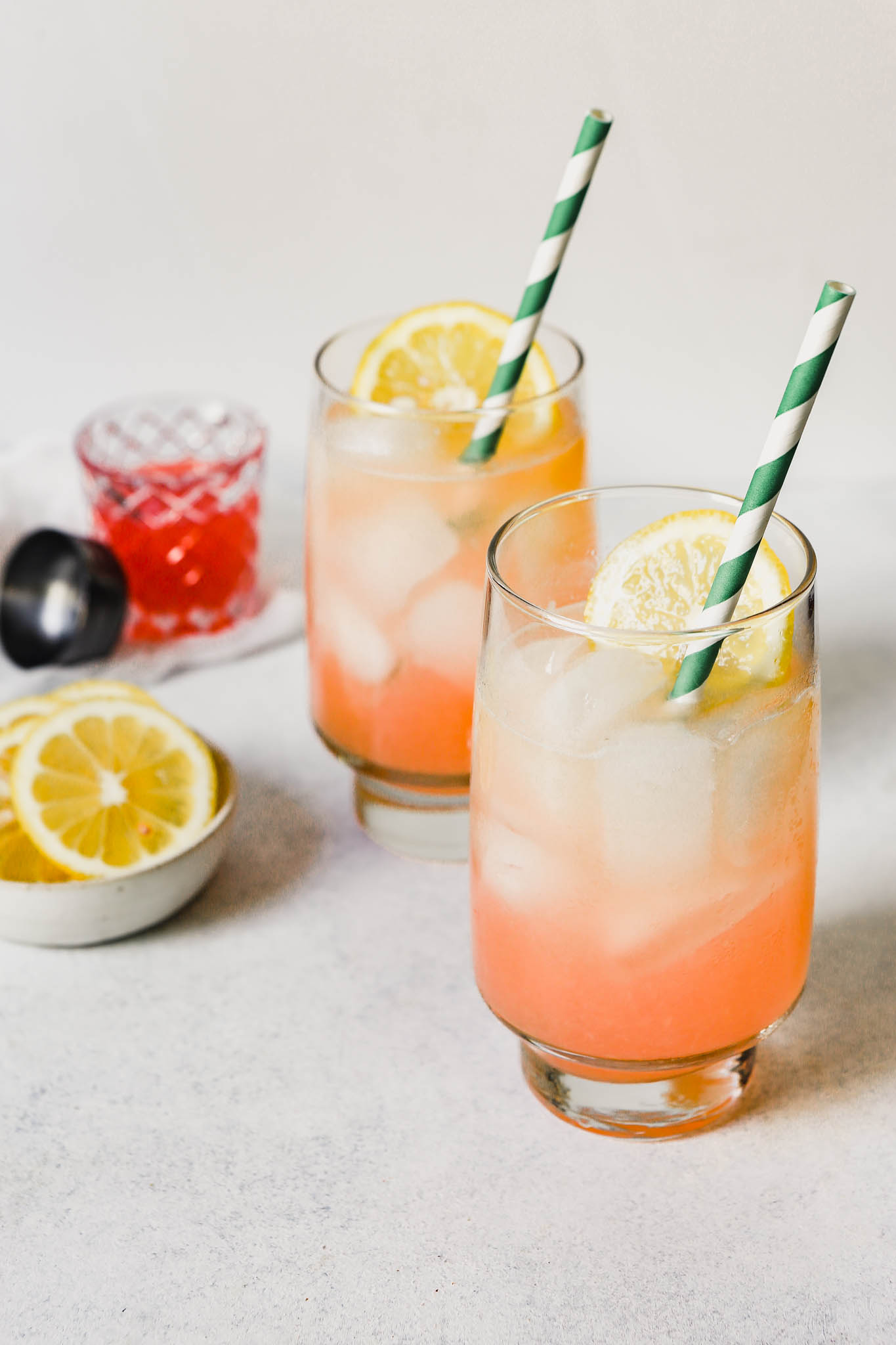 Photograph of rhubarb fizz in tall glasses with stripped green straws