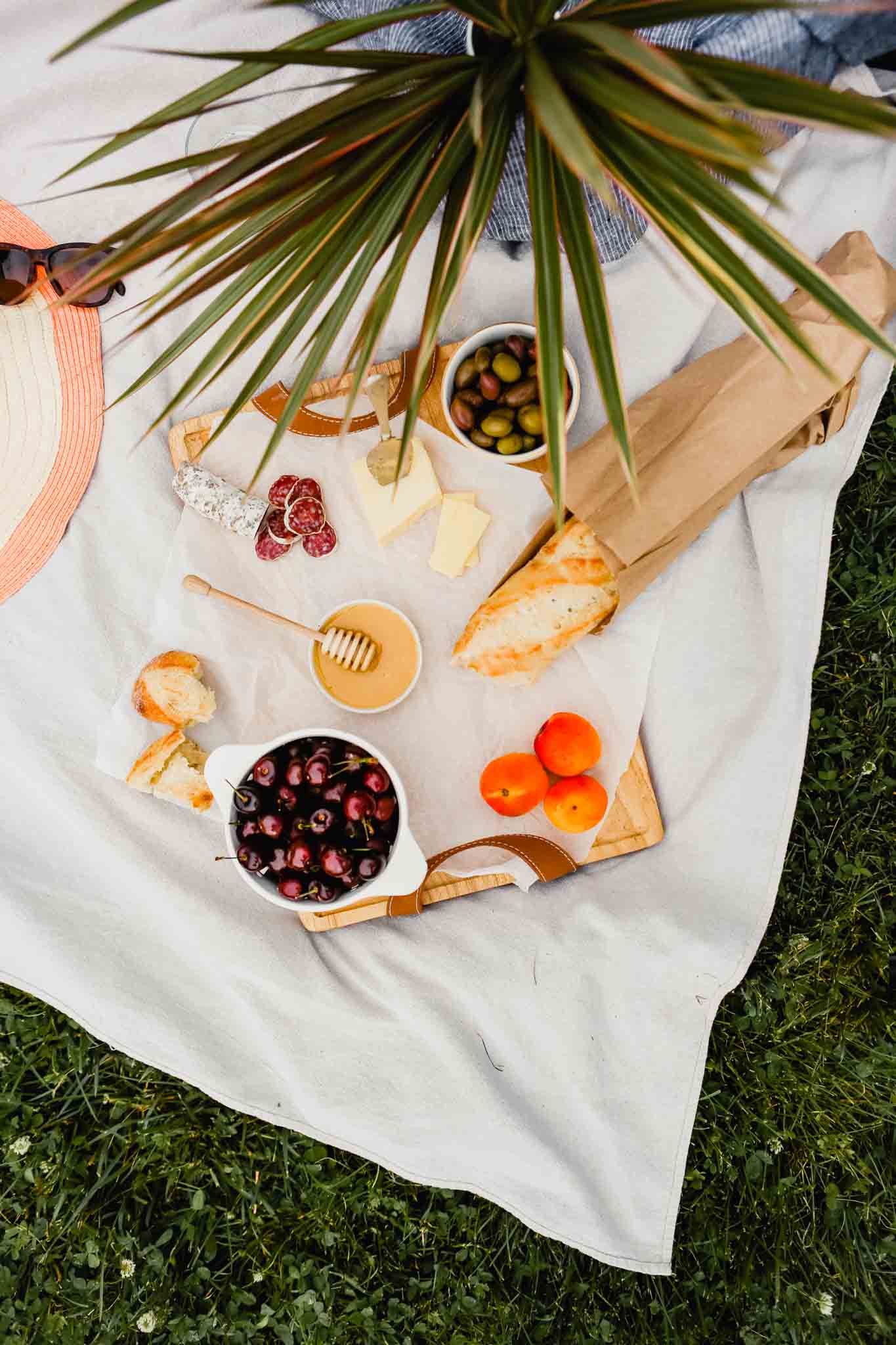 Overhead photograph of picnic spread on a white blanket on grass