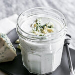Photograph of blue cheese salad dressing in a glass jar set on a gray plate on a marble table.