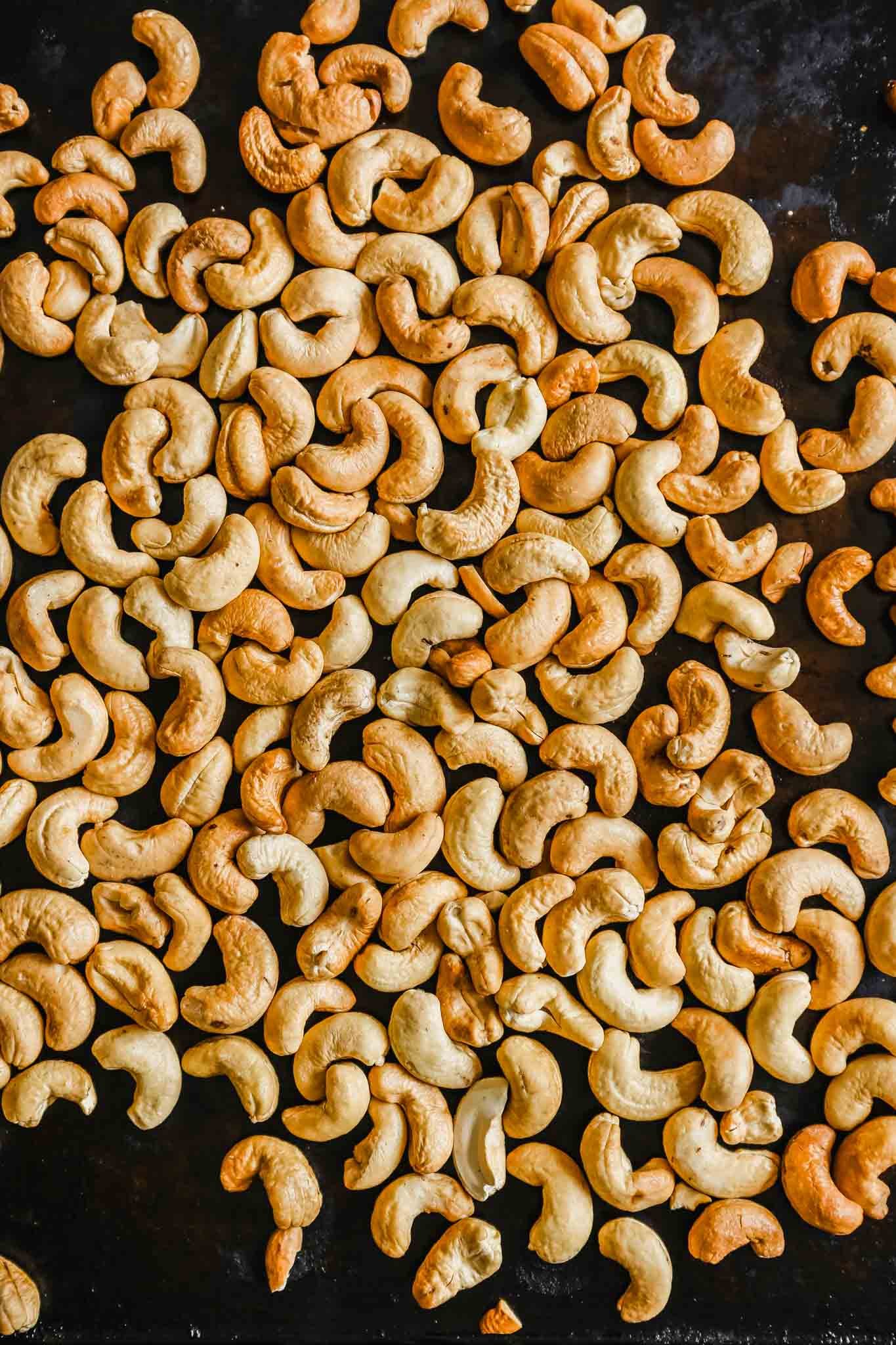 Photograph of whole roasted cashews on a dark baking sheet