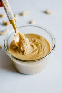Photo of creamy cashew butter in a glass bowl with a gold spoon in it