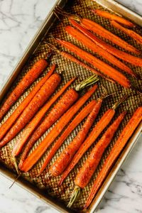 Photograph of roasted halved carrots on a baking sheet