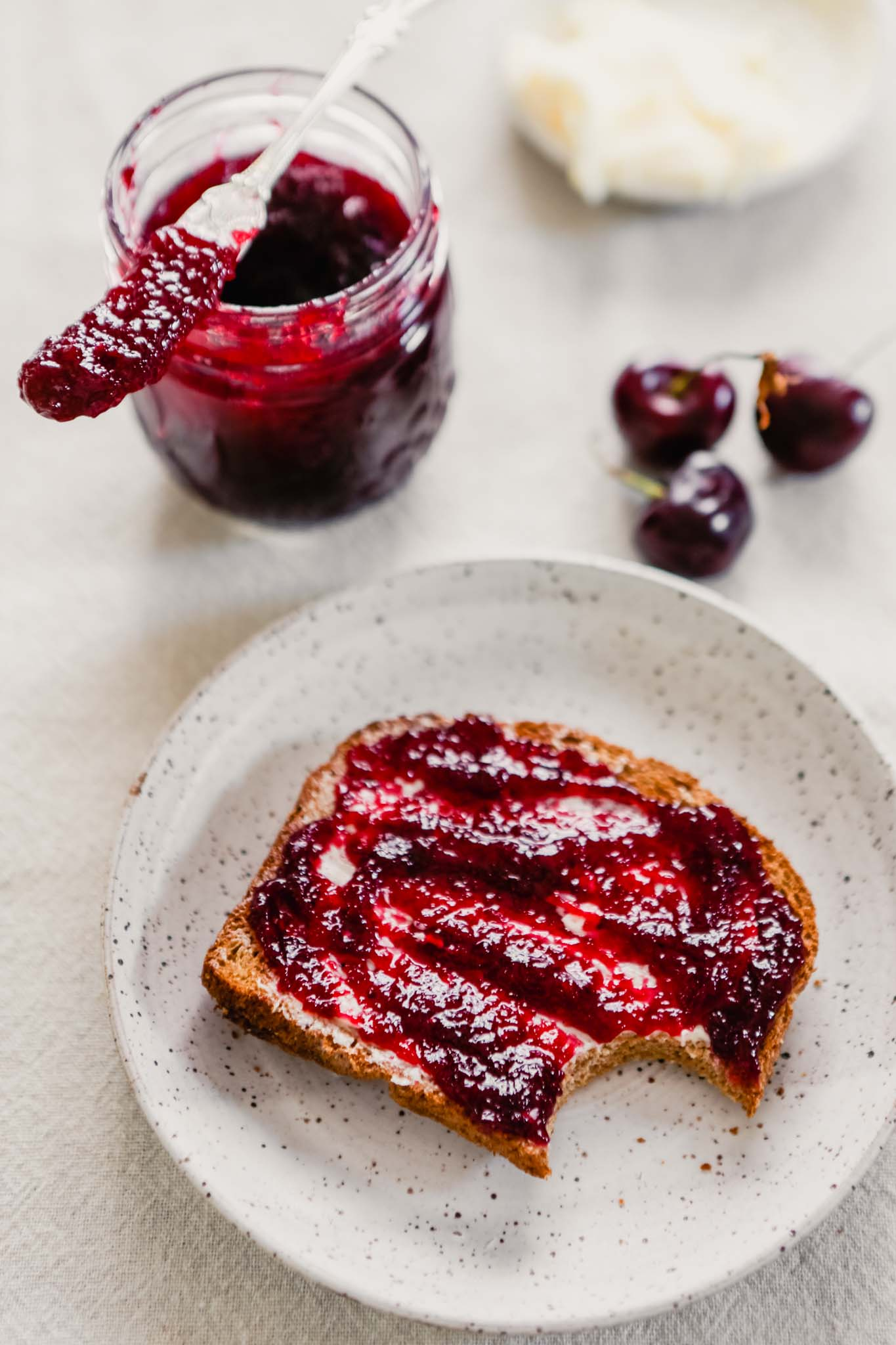 Homemade cherry jam spread onto a piece of buttered toast
