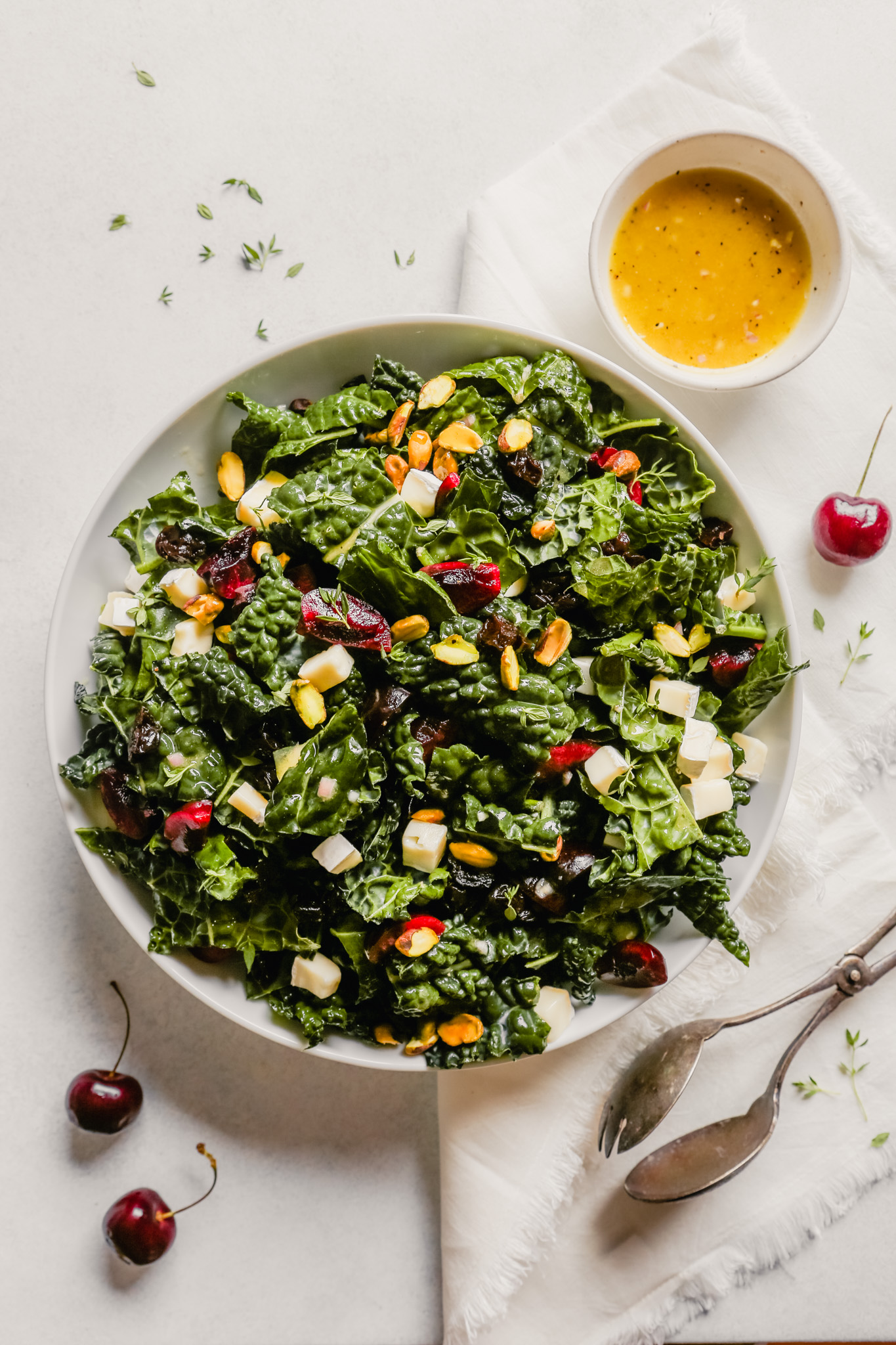Photograph of a kale salad with cherries and pistachios in a white bowl on a blue table