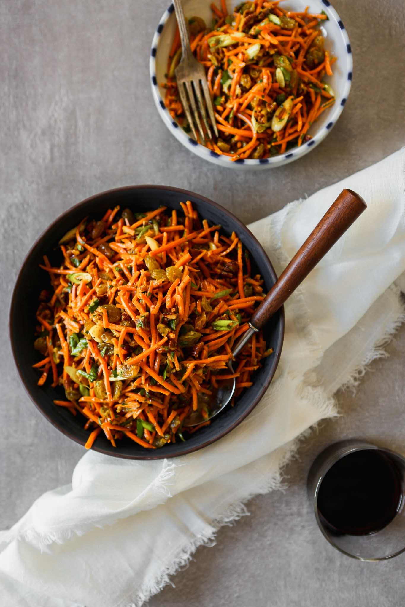 Photograph of shredded Moroccan carrot salad in a dark blue bowl set on a gray table.
