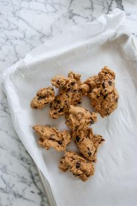cookie dough chunks on a parchment lined baking sheet