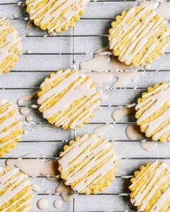Iced pumpkin cookies set on a wire rack with glaze all over coutertop