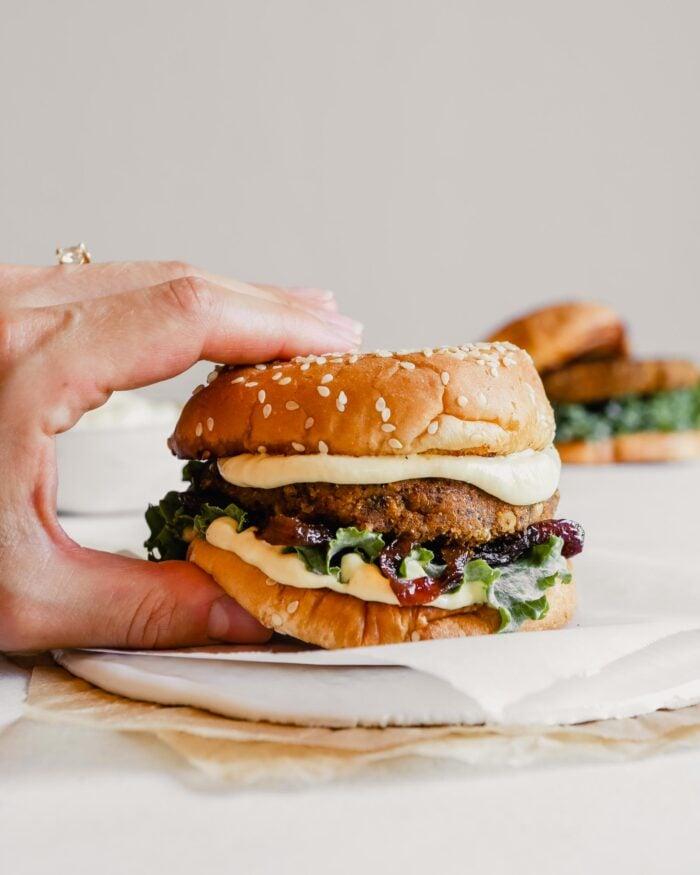Photograph of someone picking up a vegan mushroom veggie burger on a white plate
