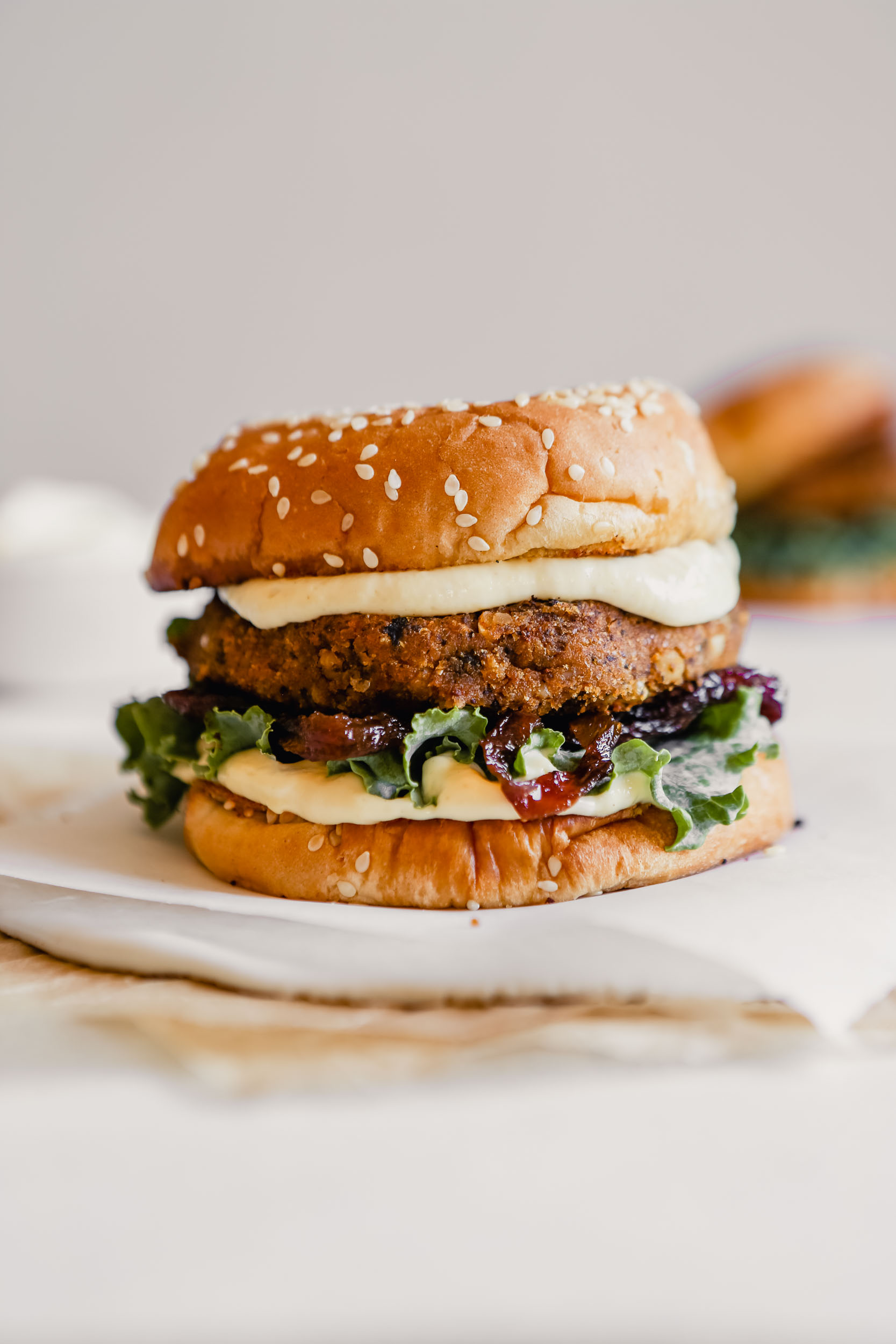Photograph of a vegan mushroom veggie burger set on a white plate