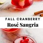 Photograph of two glasses of fall cranberry sangria set on a marble platter with a pitcher of sangria in the background.