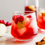 Close up Photograph of a cranberry sangria, featuring fresh cranberries and apple chunks, set on a marble platter.