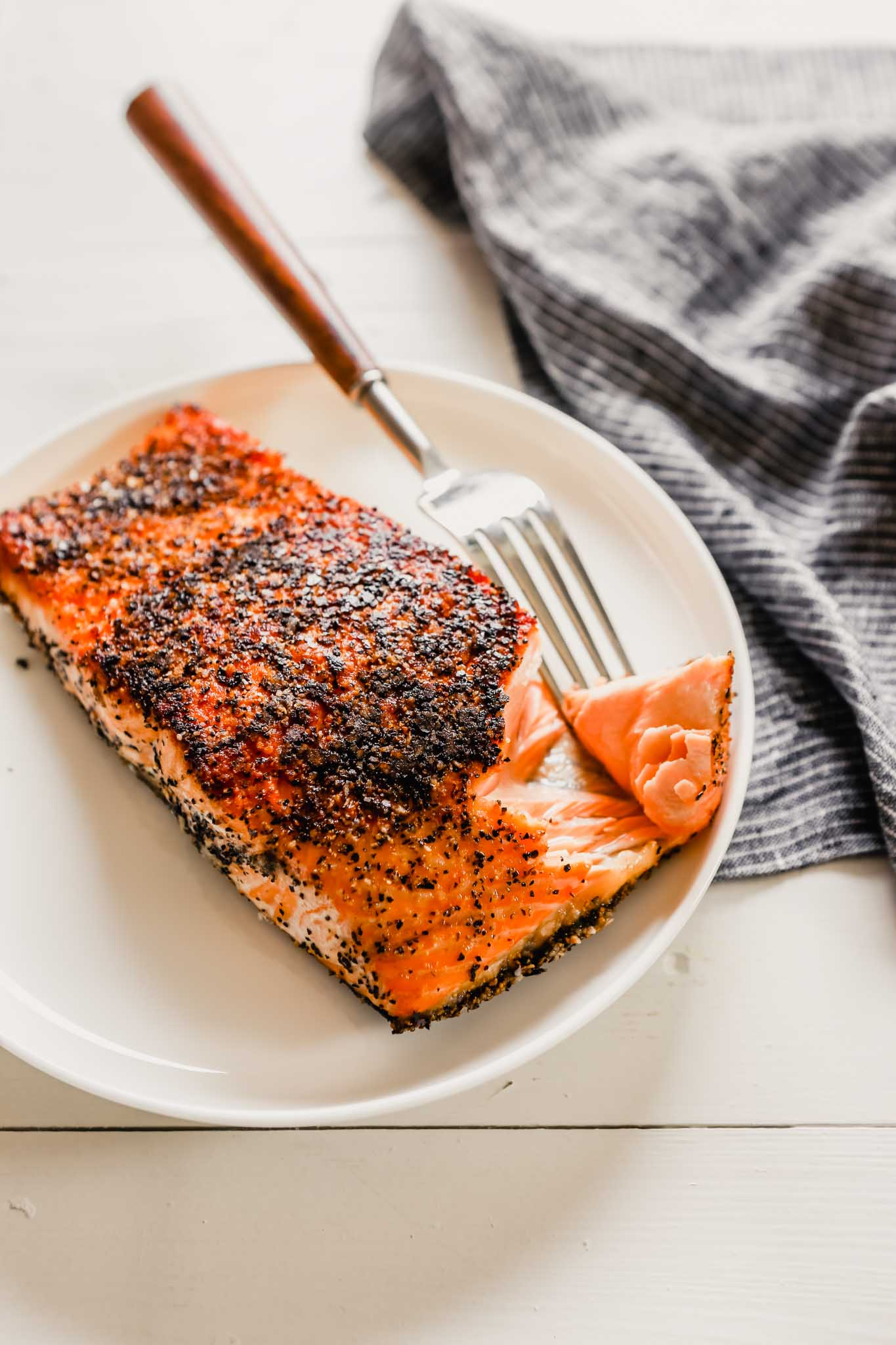 45-degree angle photo of crispy seared salmon on a white plate with a fork taking a piece off of it
