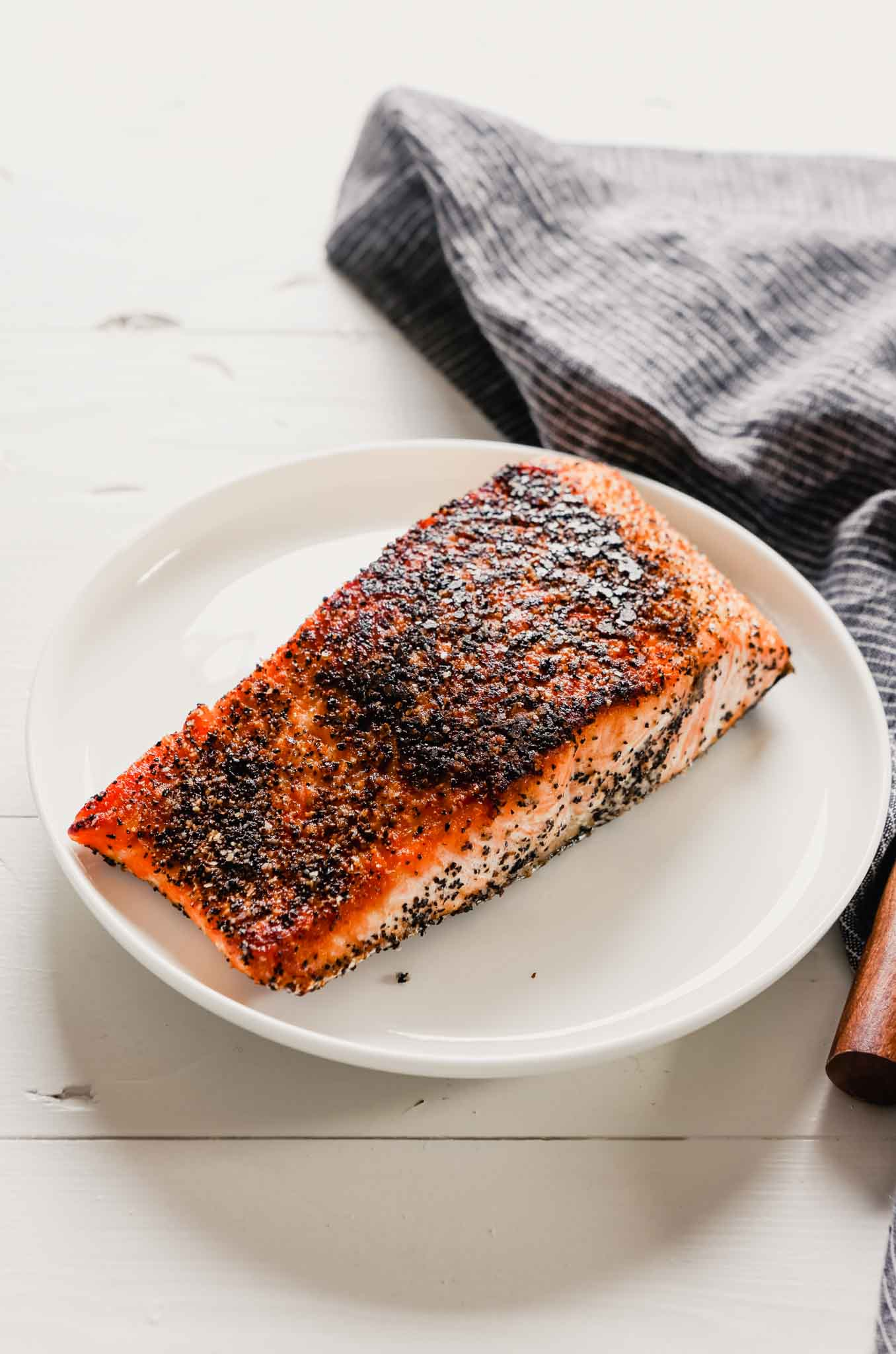 Photo of crispy pan seared salmon with skin set on a white plate with a blue napkin off to the side.