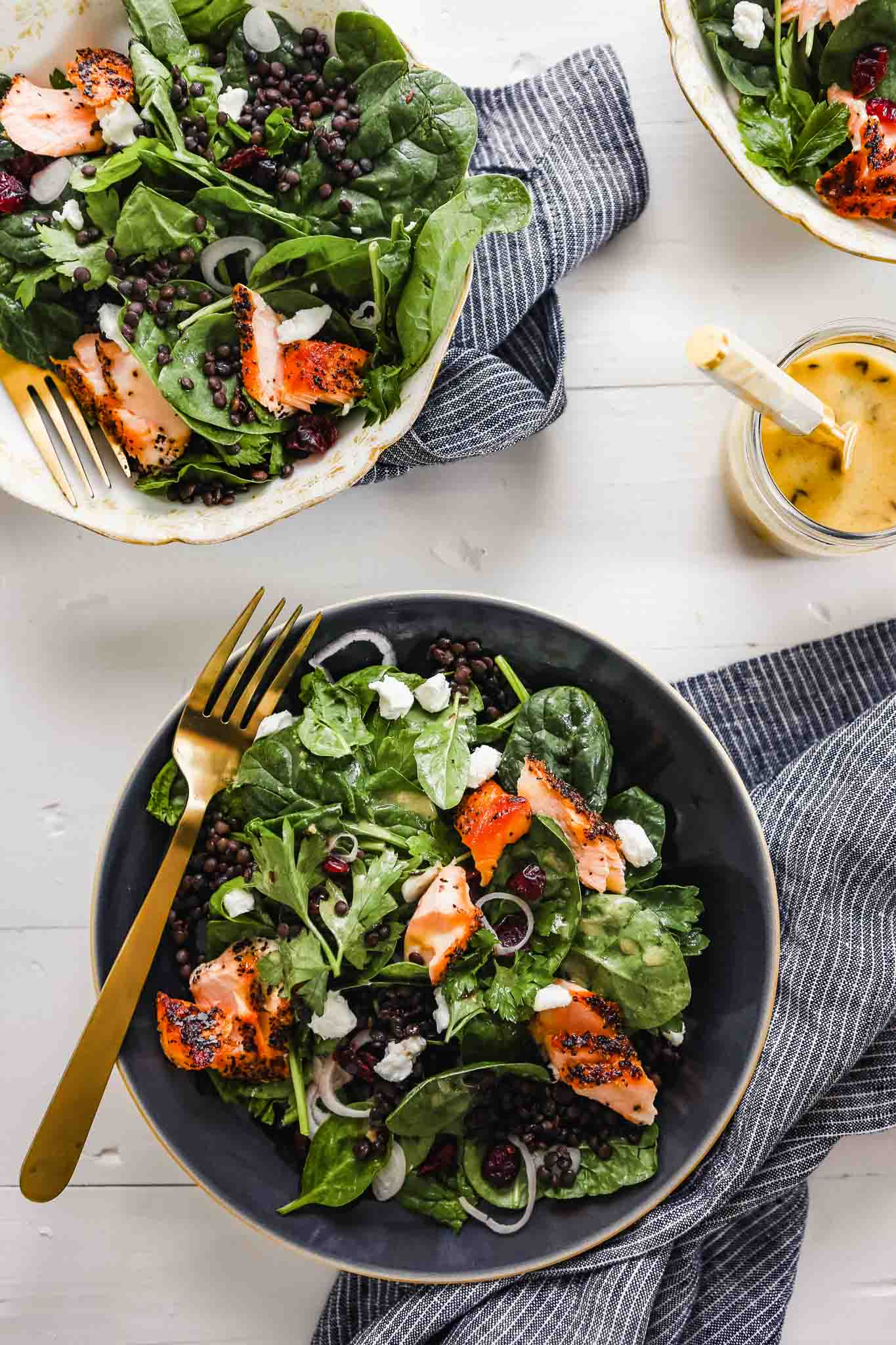 Overhead photograph of lentil and spinach salad with flakes of salmon in a dark blue bowl with a gold fork. Dressing set off to the side in a bowl with a spoon.
