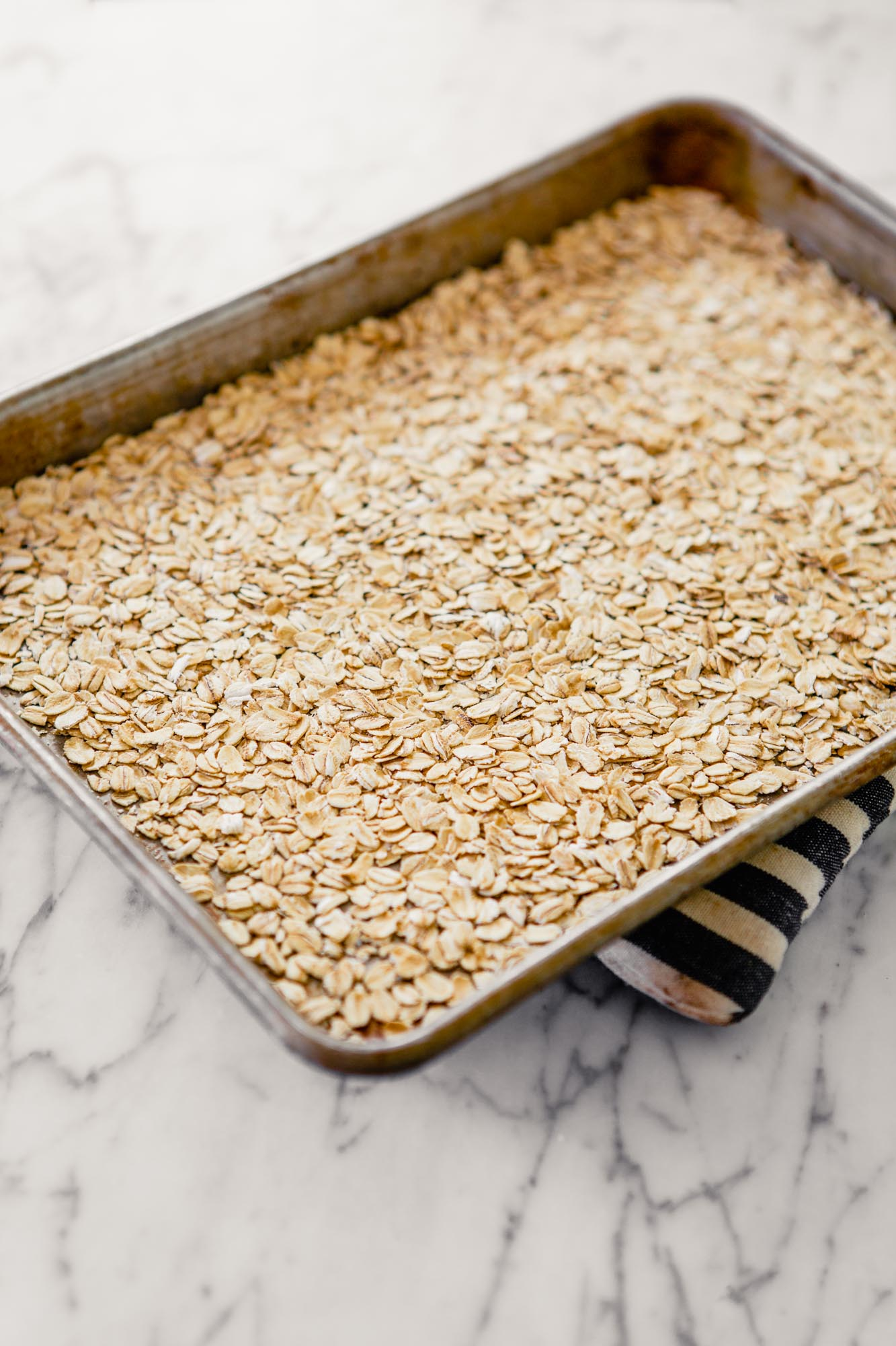 Photo of toasted oats on a baking sheet.