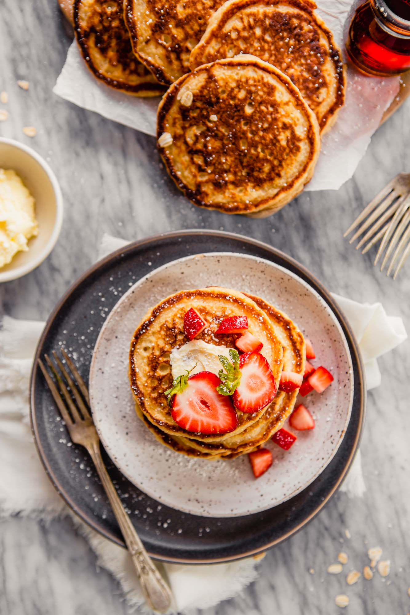 Overhead photo of pancakes stacked on a plate and pancakes arranged on a wooden platter with butter and maple syrup off to the side.