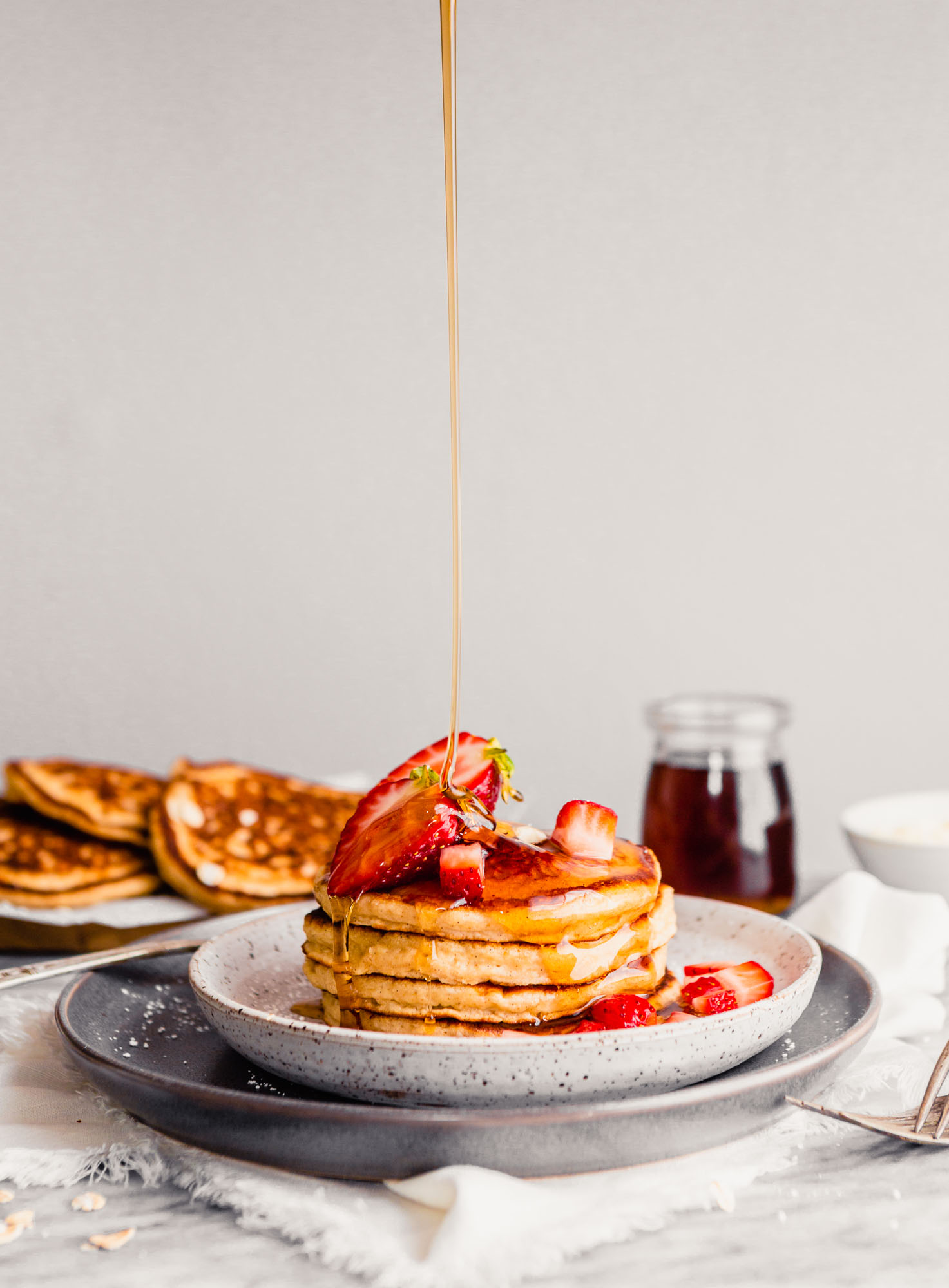 Photo of maple syrup drizzling over toasted oat pancakes stacked on a plate topped with butter and strawberries