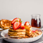Photo of a bite take out of a stack of toasted oat pancakes on a plate topped with butter, strawberries and maple syrup