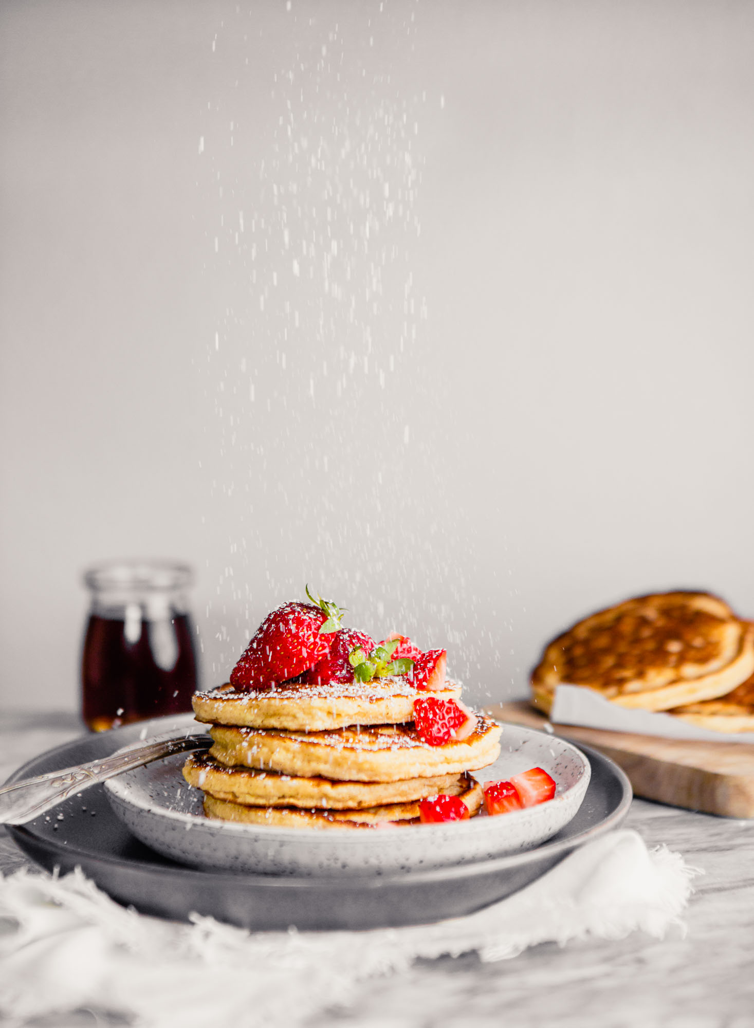 Photo of toasted oat pancakes stacked on a plate topped with butter and strawberries with powdered sugar falling down over top.