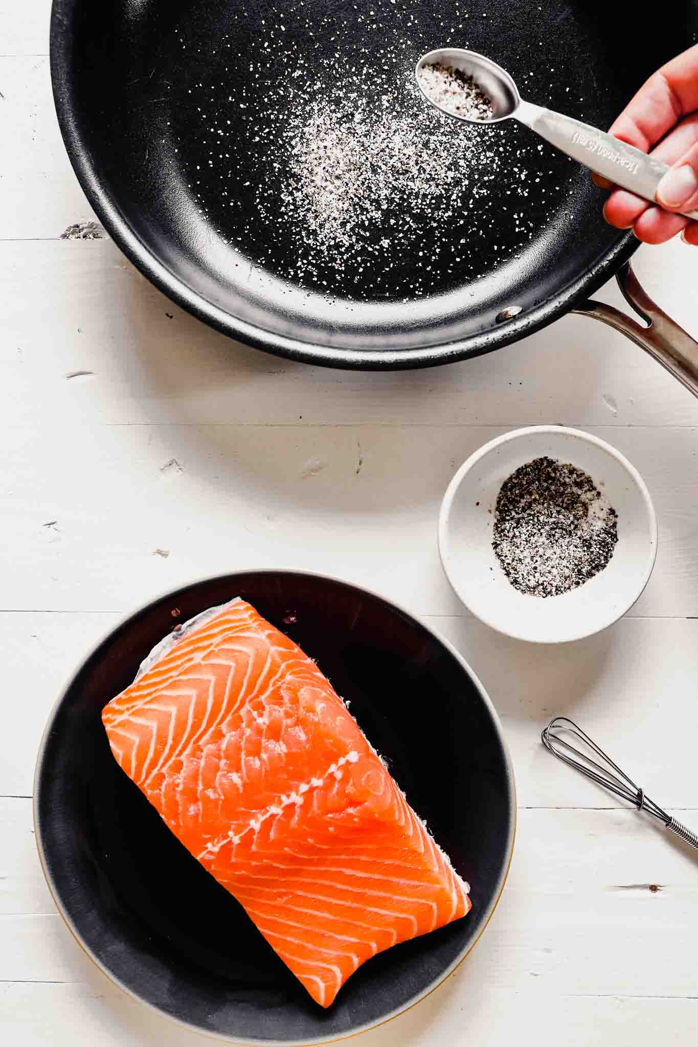 overhead image of a filet of salmon on a dark plate with a skillet up to the top and someone sprinkling salt and pepper into the skillet.