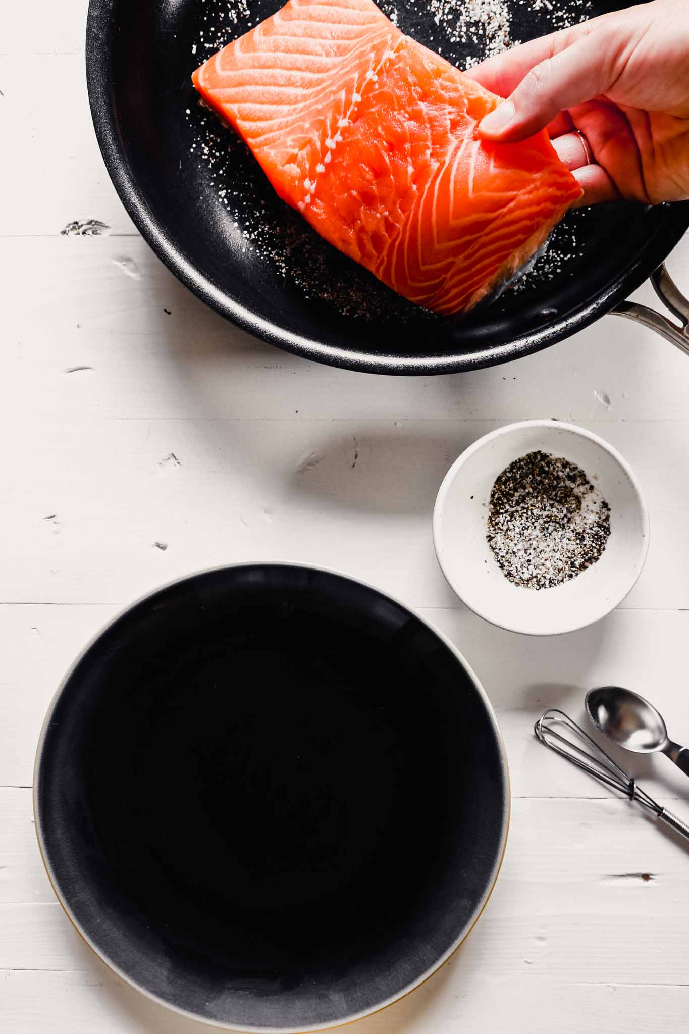 Photo of someone placing a filet of salmon into a nonstick skillet sprinkled with salt and pepper.