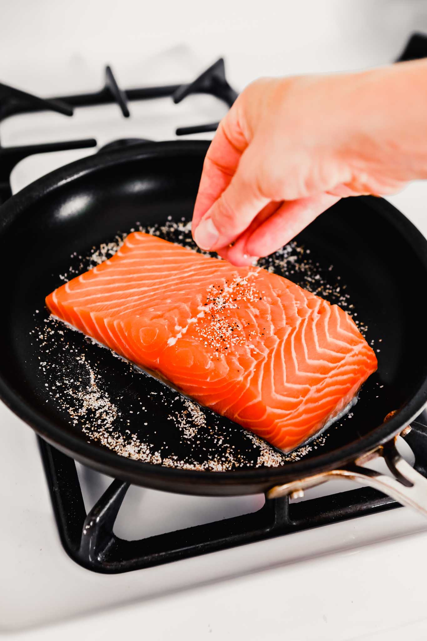 Photo of someone sprinkling a filet of salmon with salt and pepper.