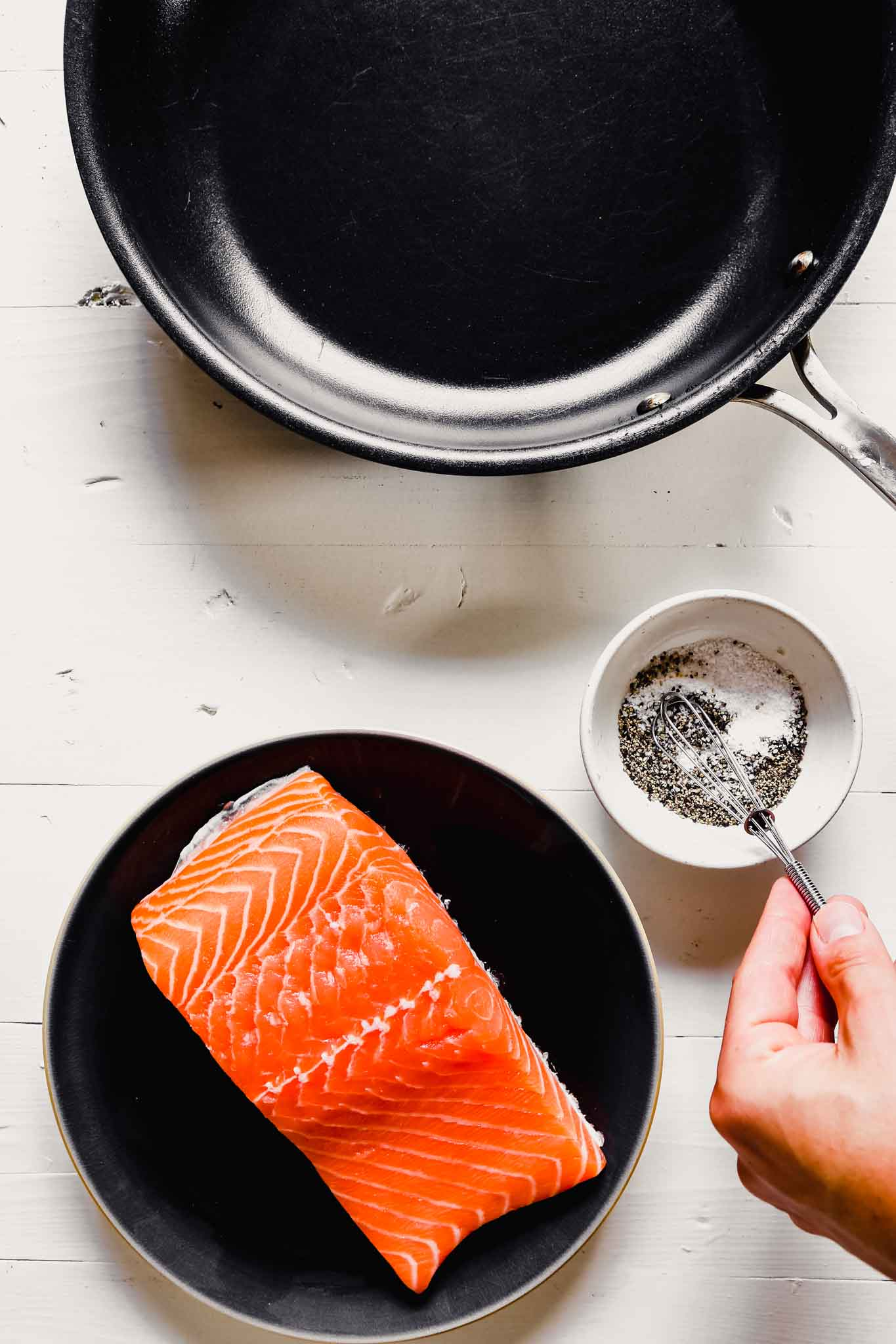 overhead image of a filet of salmon on a dark plate with a skillet up to the top and someone whisking salt and pepper together in a small bowl.