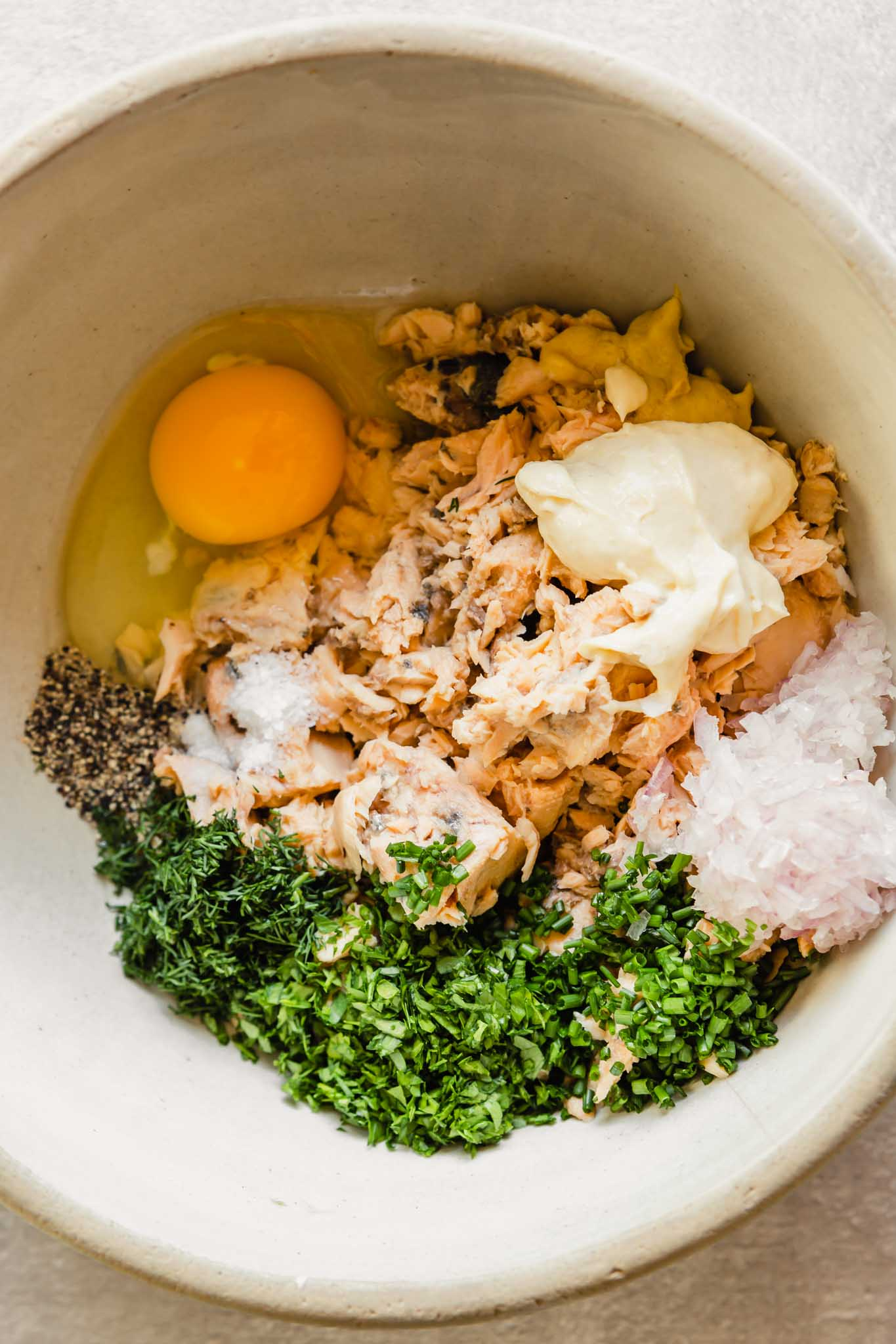 Overhead photo of salmon cake ingredients (egg, salmon, herbs, shallot, mayo, salt and pepper)in a large bowl.