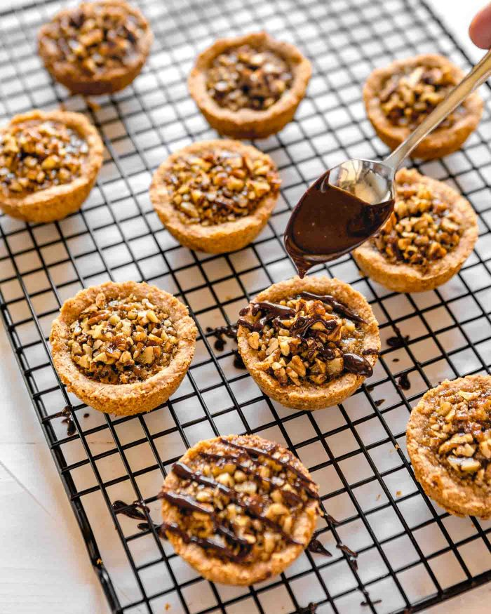 Mini pecan tarts being drizzled with a semi-sweet chocolate ganache