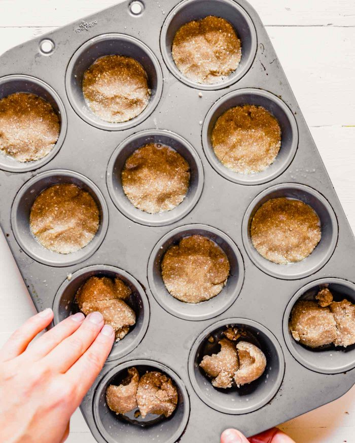 overhead image of dough being pressed into a muffin tin