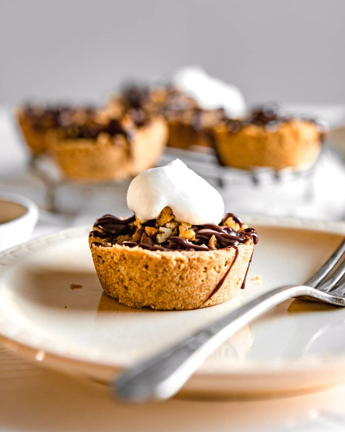 Side angle of a mini pecan pie topped with a dollop of whipped cream on a cream-colored plate