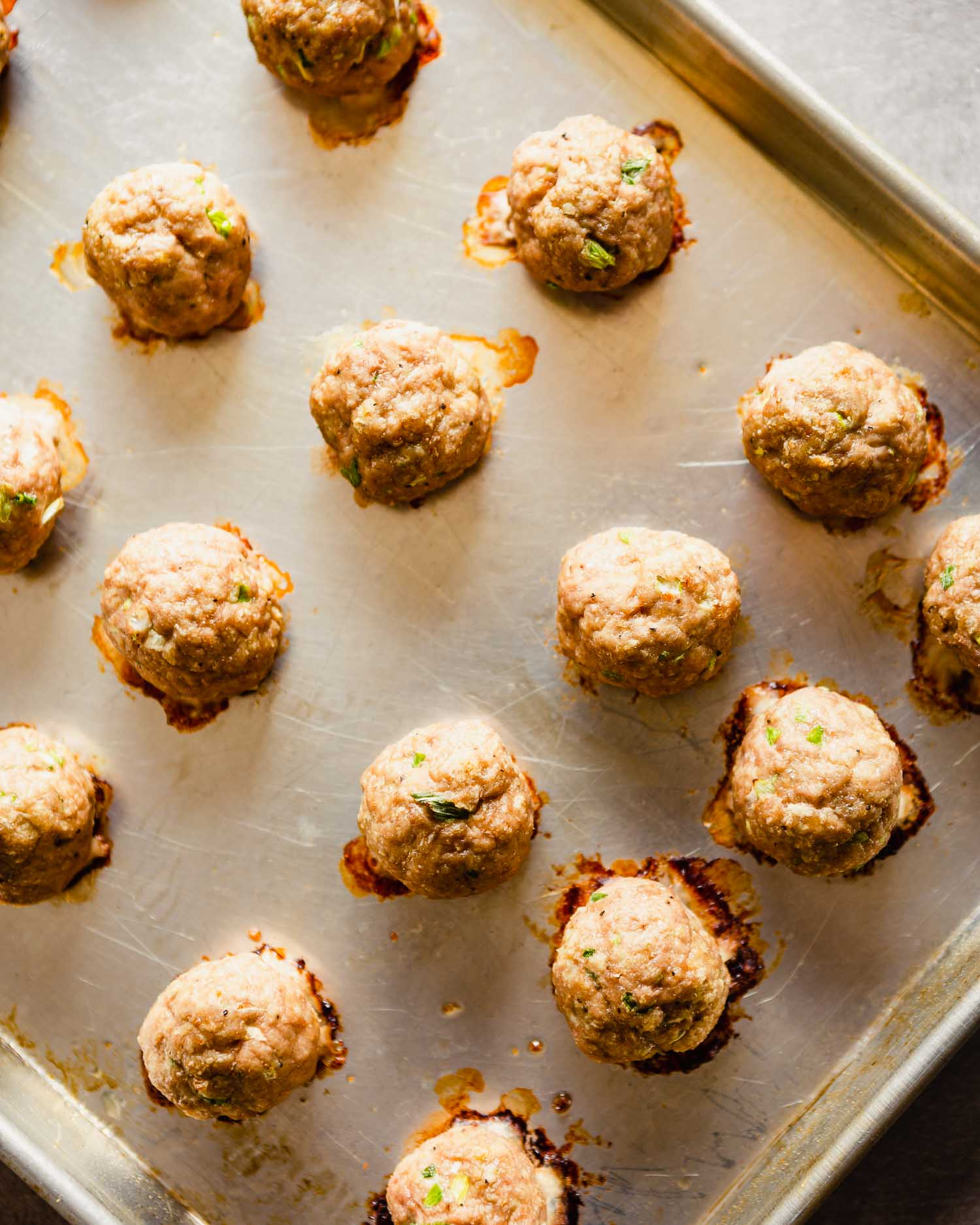 Overhead of baked turkey meatballs on a baking sheet