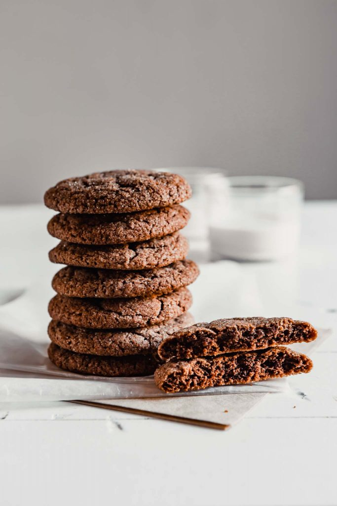 photo of chocolate cookies stacked on a white table with milk set in the background