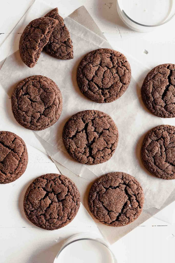 Overhead image of chocolate cookies arranged on a white table with glasses of milk set around them