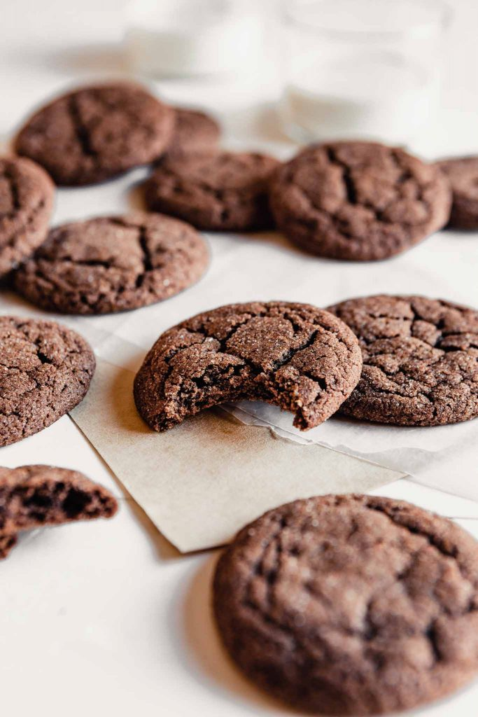 Side angle of a chewy chocolate cookie with a bite taken out of it arrange on a table with other cookies