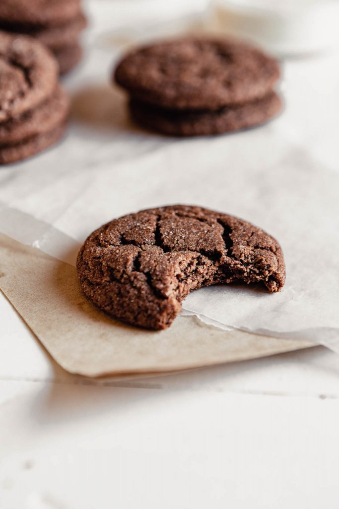 Side angle of a chewy chocolate cookie set on a white table with a bite taken out of it