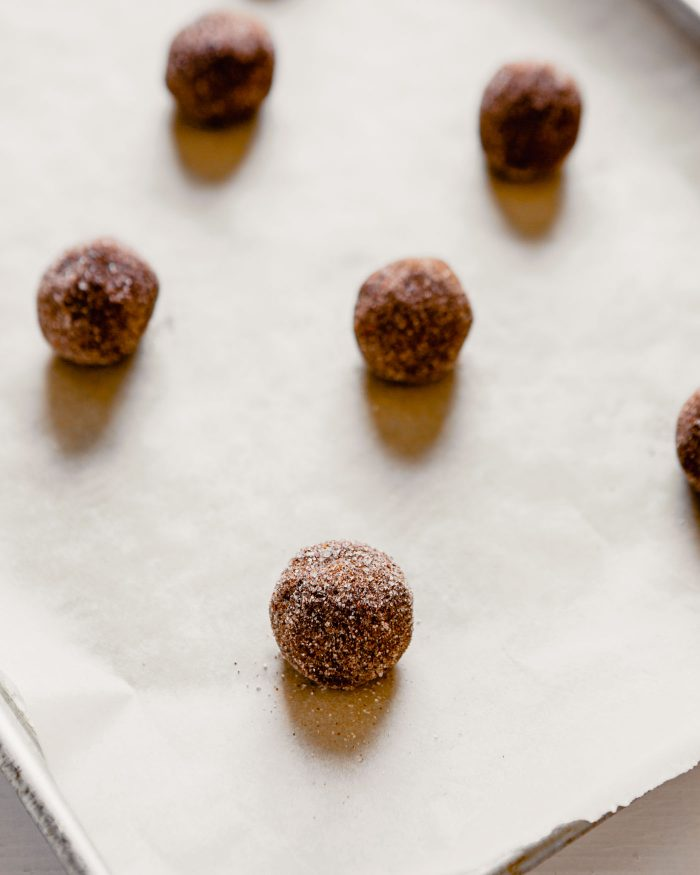 photo of chocolate dough balls coated in a sugar mixture set on a parchment-lined baking sheet