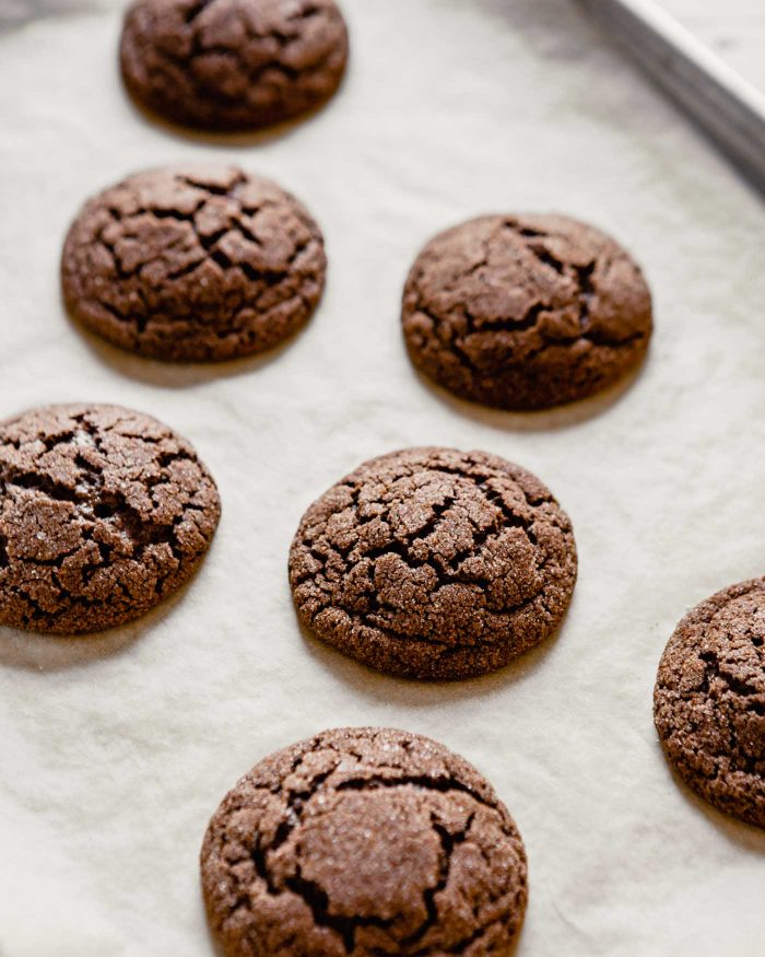 photo of baked chocolate snickerdoodles on a parchment lined baking sheet