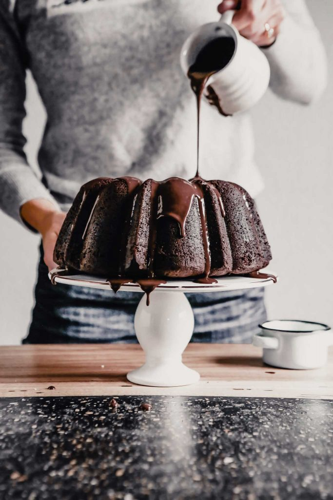side angle of chocolate glaze being drizzled by someone over a chocolate cake on a cake stand